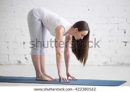 Attractive young woman working out indoors. Side view portrait of beautiful model doing yoga exercise on blue mat. Standing in Ardha Uttanasana (Standing Half Forward Bend pose). Full length - stock photo