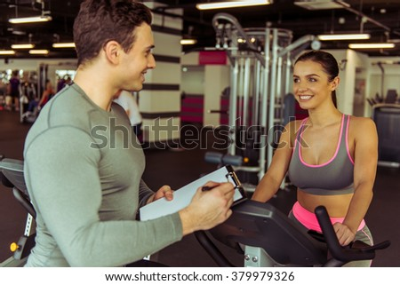 Attractive young woman working out on an exercise bike in gym, muscular trainer making notes. Both smiling - stock photo