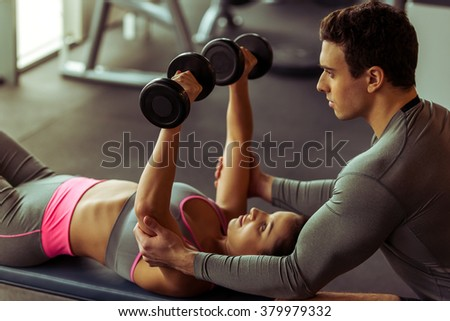 Attractive young woman working out with dumbbells in gym, handsome muscular trainer helping her - stock photo