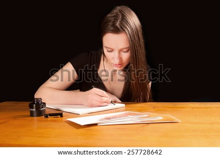 Attractive young woman writing a letter at an old table - stock photo