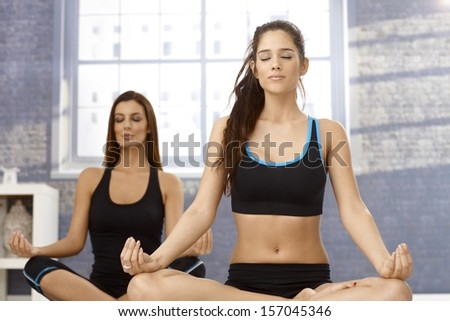 Attractive young women sitting in tailor seat eyes closed, practicing yoga, meditating. - stock photo