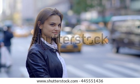 attractive young women standing on city street. happy smiling female model. urban city background - stock photo