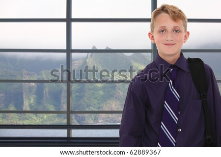 Attractive young 12 year old boy in dress shirt and tie with shoulder bag in front of window in Hawaii. - stock photo