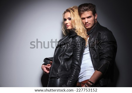 Attrative young fashion man holding his girlfriend while leaning on a grey wall, both looking at the camera. - stock photo