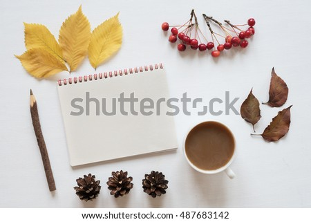 Attributes of autumn, coffee and notebook on a white board