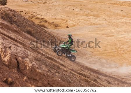 ATV rider uphill in the desert in summer - stock photo