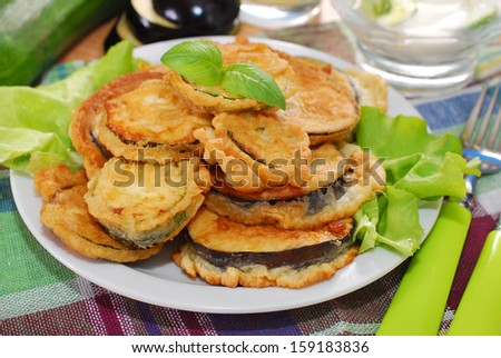 aubergine and zucchini slices fried in batter for lunch - stock photo