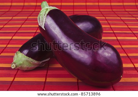 aubergine vegetable on the red background - stock photo