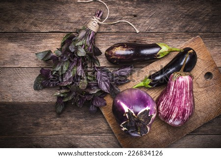Aubergines and basil on chopping board and wooden table. Rustic style and autumn food photo - stock photo