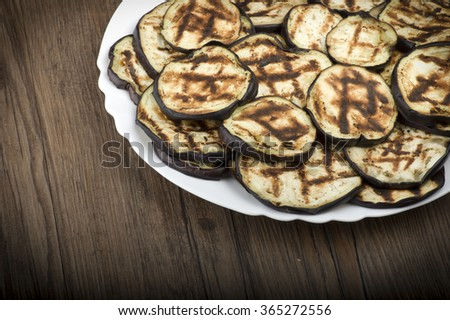 Aubergines eggplants and slices grilled on the plate - stock photo
