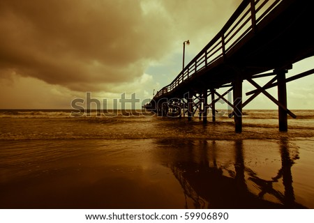 Auburn storm clouds role in over a quiet fishing pier on Myrtle Beach - stock photo
