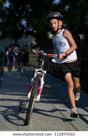 AUCH, FRANCE - SEPTEMBER 8: an unidentified young  runner in the transition area, Auch Triathlon for children, on September 8, 2012 in Auch, France.