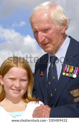 AUCKLAND - APRIL 25: A World War 2 veteran stands with his unidentified grand daughter following the annual ANZAC Day remembrance service, on April 25, 2007 in Auckland, New Zealand. - stock photo