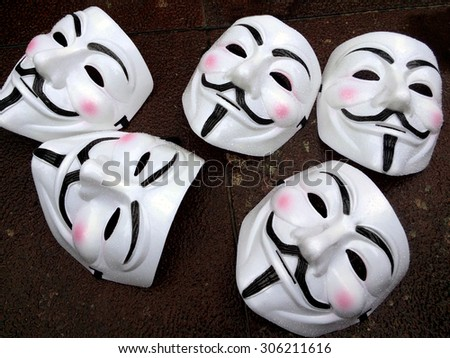 "AUCKLAND - AUG 15 2015:Guy Fawkes masks on the ground during a public protest. In 2012, Time called Anonymous one of the ""100 most influential people"" in the world. - stock photo"