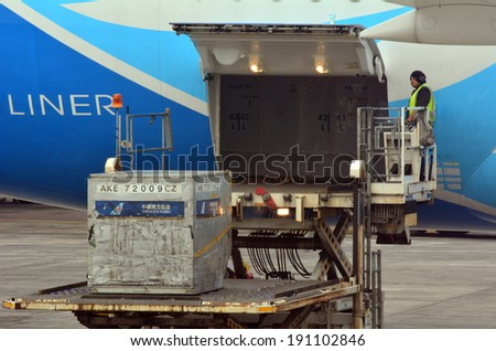 AUCKLAND, NZ - APR 10 2014:Cargo man on loading platform load air freight to cargo aircraft. - stock photo