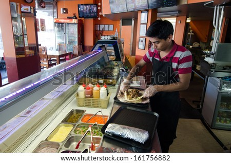 AUCKLAND, NZ - OCT 07:Man prepare doner kabab on Oct 07 2013.It's and Ottoman a Turkish dish from the 18th century. The Greek gyro, Arab shawarma, and Mexican taco al pastor are derived from this dish - stock photo