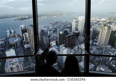 AUCKLAND, NZ - OCT 08: Visitors at the Sky Tower observation deck on Oct 08 2013..It's 328 metres (1,076ft) tall and it the tallest free-standing structure in the Southern Hemisphere. - stock photo