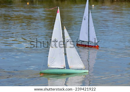 AUCKLAND, NZL - DEC 21 2014:Two remote controlled sailing wooden yachts race in a pond.The racing is governed by the same Racing Rules of Sailing that are used for full-sized crewed sailing boats - stock photo