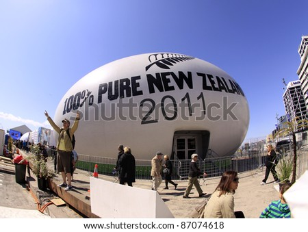 AUCKLAND- SEPT. 23: Tourists and locals gather around to view the giant rugby world cup ball at the Auckland Viaduct in Auckland, New Zealand on Friday September 23, 2011. - stock photo