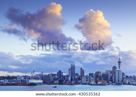 Auckland Skyline at twilight, with dramatic sunlit clouds.