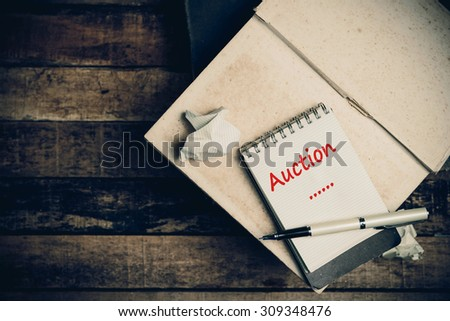Auction on pages sketch book on wood table vertical  - stock photo