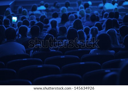 Audience in the cinema. Silhouette shot from back in blue light. - stock photo