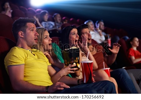 Audience sitting in multiplex movie theater, watching horror movie, screaming. - stock photo
