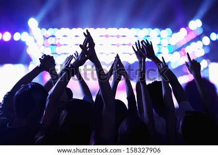 Audience watching a rock show with hands in the air - stock photo