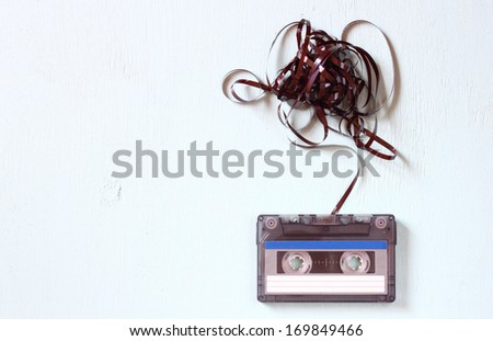 Audio cassette tape with subtracted out tape over blue textured wood board - stock photo