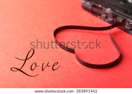Audio cassette with magnetic tape in shape of heart on red background