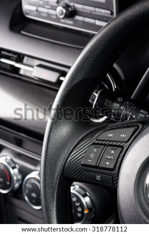 audio control bottons on steering wheel of modern car - stock photo