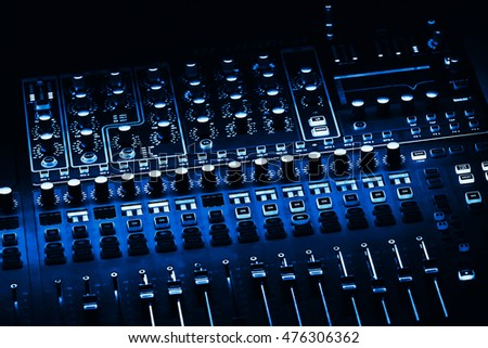 Audio mixer mixing board fader and knobs. Blue colored.