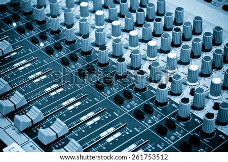 audio mixing console with faders and adjusting knobs - stock photo