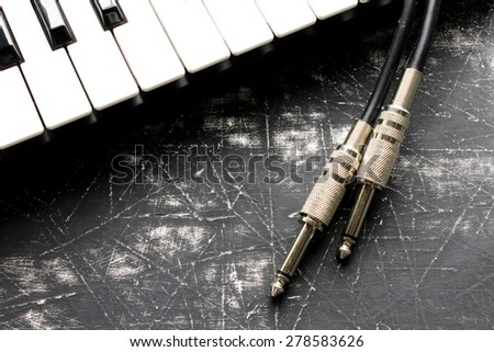 Audio plug and piano keys - stock photo