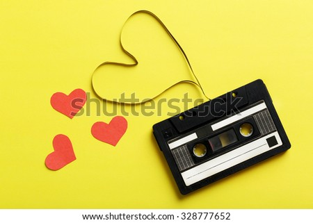 Audio tape cassette on yellow paper background - stock photo