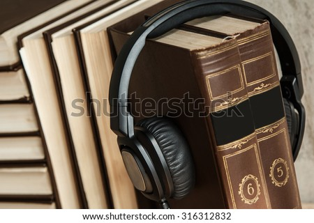 Audiobooks concept. Old books and black headphones