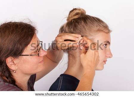 Audiologist inserting a hearing aid in an ear of a young woman