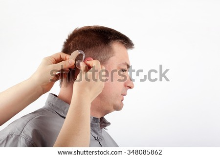 Audiologist's hands inserting a middle-aged man's hearing aid into his ear - stock photo