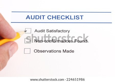 Audit checklist and human hand with pencil. - stock photo
