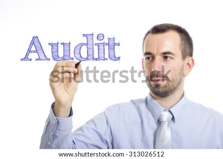 Audit - Young businessman writing blue text on transparent surface - stock photo
