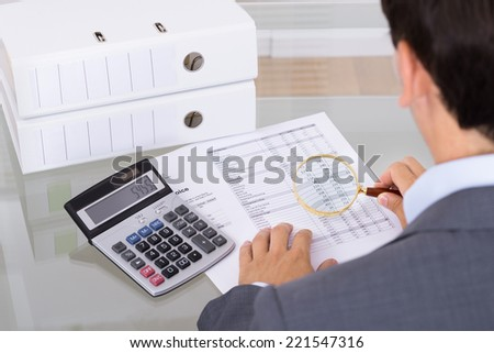 Auditor investigating fraud with magnifying glass. Over the shoulder view - stock photo