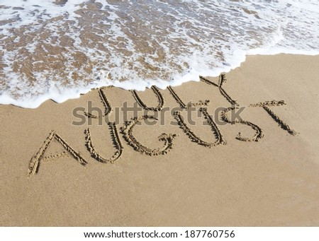 August is coming concept - inscription July and August  written on a sandy beach, the wave is starting to cover the word July.  - stock photo