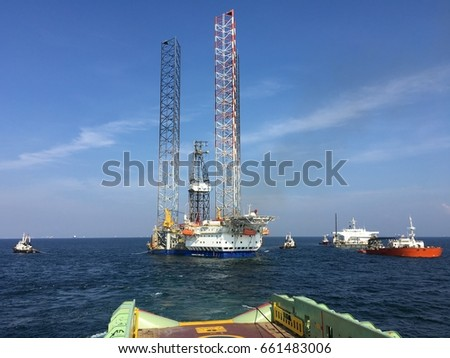 August 15, 2016 Labuan, Malaysia - A jack up rig being towed by tug vessel into heavy-lift ship, transporting to other oil field for drilling.