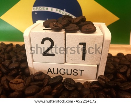 August 21st. Image of august 21 wooden white color calendar on Brazil flag and coffee beans background. Summer day.