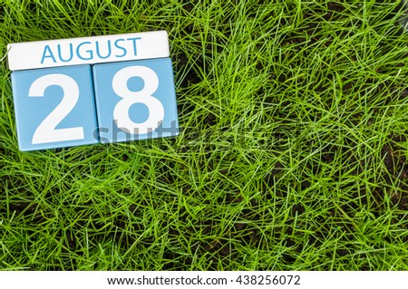 August 28th. Image of august 28 wooden color calendar on green grass lawn background with soccer ball. Summer day. Empty space for text - stock photo