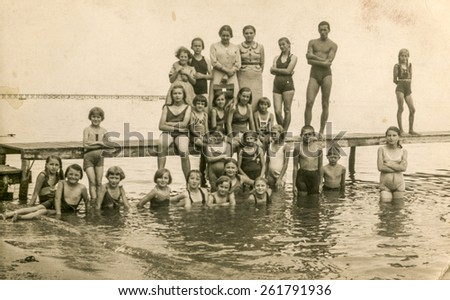 AUGUSTOW, POLAND, CIRCA 1950s: Vintage photo of group of children resting on lakeside with their tutors - stock photo