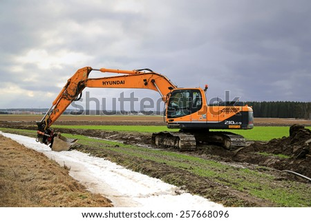AURA, FINLAND - MARCH 1, 2015: Hyundai Robex 210LC-9 Crawler Excavator on a field. The R210LC-9 has  horizontal reach of 10,9 m and dregding depth of 7,7 m. - stock photo