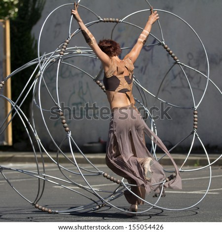 AURILLAC, FRANCE - AUGUST 22: a dancer moves in the middle of a metallic structure as part of the Aurillac International Street Theater Festival, Cie Eclektic,on august 22, 2013, in Aurillac,France  - stock photo