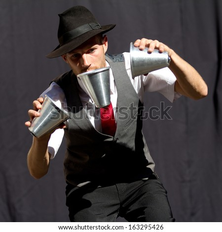 AURILLAC, FRANCE - AUGUST 22: A juggler is playing with three cups as part of the Aurillac International Street Theater Festival, Cie Kiblos,on august 22, 2013, in Aurillac,France  - stock photo