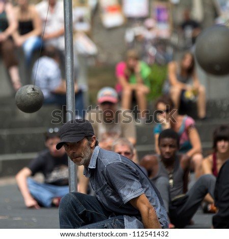 AURILLAC, FRANCE - AUGUST 24: a man looks after a heavy ball which is moving towards him, Aurillac International Street Theater Festival, show named New town, on august 24, 2012, in Aurillac,France.